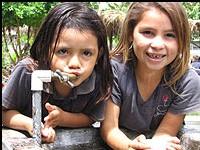 Deux  petites filles boivent au robinet d'un forage profond récemment creusé dans une école primaire de La Paz au Salvador. L'eau de surface contaminée tue des milliers de gens chaque année dans le pays et la plupart des victimes sont des enfants. NP
