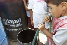 Un jeune enfant aspire avec peine au tuyau d'arrosage l' eau fournie par le service SEDAPAL