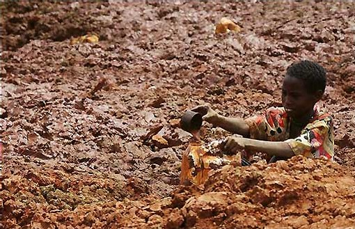 petit Kenyan creusant la terre pour récupérer quelques gouttes d'eau. Ag Gamma