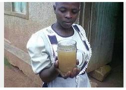 Une jeune fille dans le village de Bijaba en Ouganda central apporte un verre d'eau boueuse