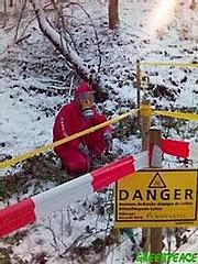 Des militants de Greenpeace équipés de combinaisons de protection mettent en sécurité des déchets toxiques à Letten