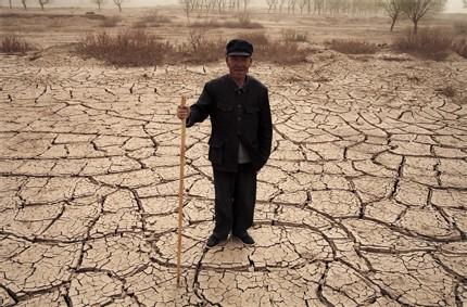 Réfugié écologique Photo : Benoît Aquin | Bourse média de l'ACDI avril 2006 – Province de Gansu, Chine - Un berger pose sur une terre asséchée, conséquence du pompage intensif de l'eau. Le désert est dorénavant libre d'avancer, condamnan