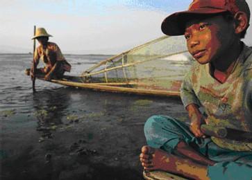 Htwe Tee, 10 ans, un pêcheur Intha, est assis sur sa barque allongée sur le Lac I nlay. Les pêcheurs du lac sont célèbres pour leur manière de pagayer avec une jambe, ce qui leur laisse les deux mains libres pour pêcher. [Photo: AFP]
